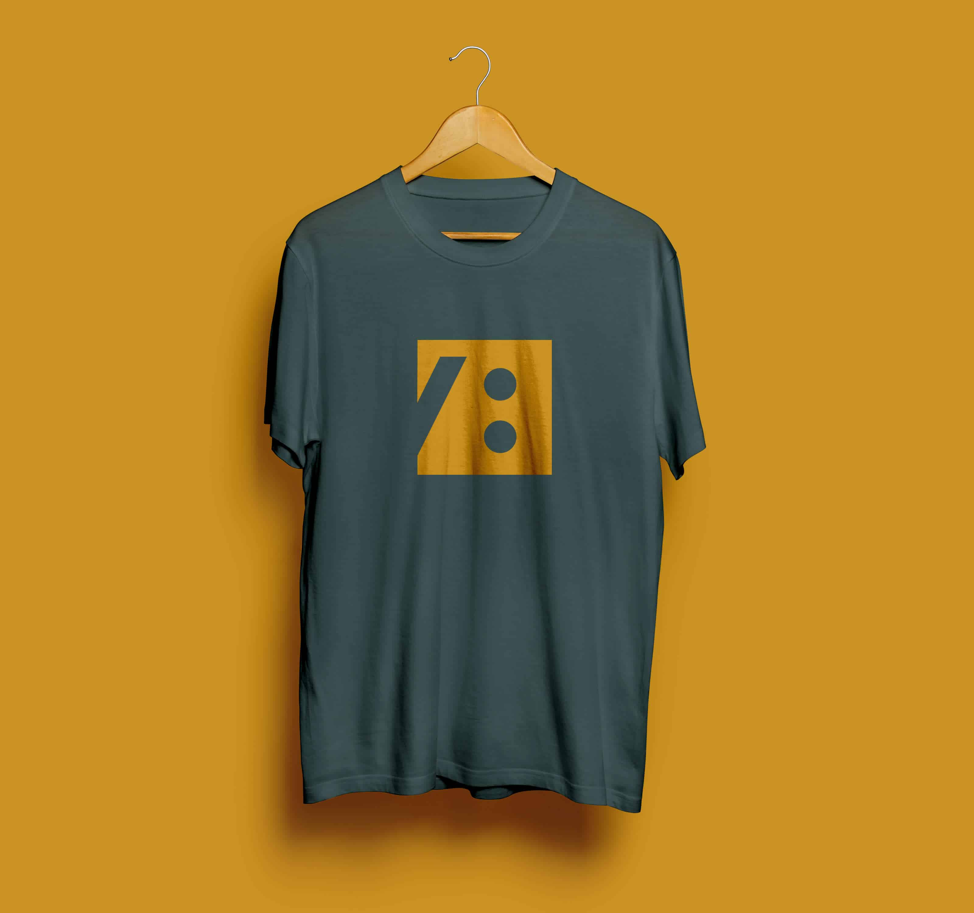 Mockup of Voisign golden coloured submark on an seaweed coloured tshirt