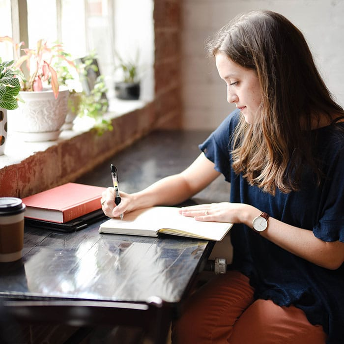 Image of a girl writing, brainstorm and strategising in a notebook by a window;