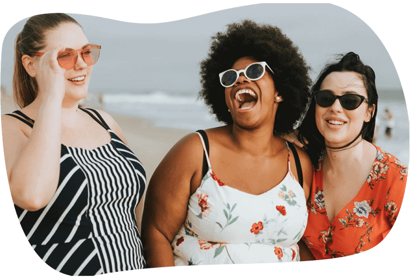 Image of three friends laughing on a beach to represent our amazing clients